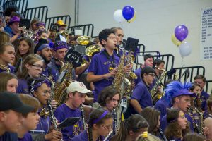 The high school band performs from the gym bleachers during the pep rally