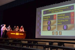 High school students play a Family Feud-style game on the high school stage