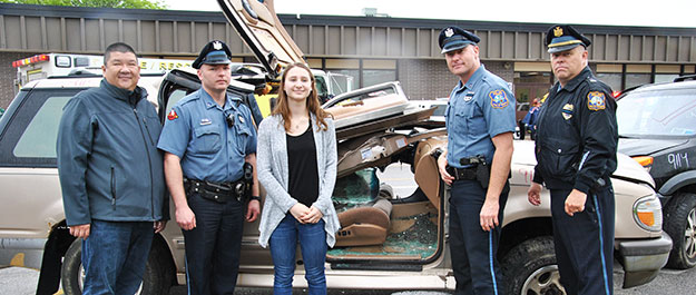 A high school girl and two uniformed police officers stand in front of a mock crash