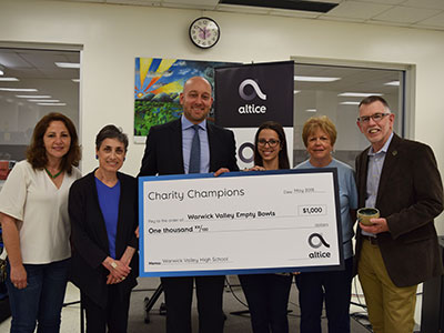 An Altice representative awarded WV Empty Bowls with a $1000 check through their Charity Champions program