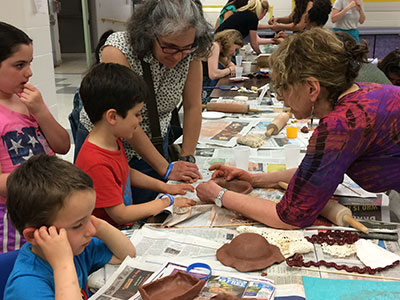 Children work on clay projects at Empty Bowls 2018
