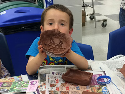 Child shows the clay bowl he made at Empty Bowls 2018