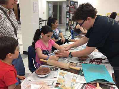 A WVHS Empty Bowls Club member helps a child with her clay bowl project