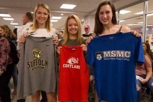 three female athletes hold up college t-shirts