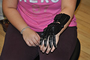 Student shows a finished prosthetic hand