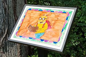 "A standing frame displays an illustration of Arthur (""Arthur"" children's book series), as part of a StoryWalk exhibit, along a wooded area."