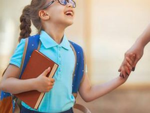 Student carrying bookbag and book holds the hand of an adult and smiles while looking upward toward the adult.