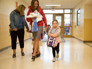 Student holding backpack walks down school hallway accompanied by teacher.