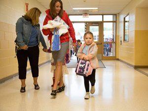 Student holding backpack walks down school hallway accompanied by teacher.