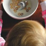 Seen from above, a young child eats a bowl of cereal
