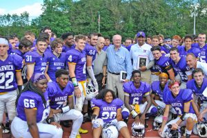 Group photo of the WV football players surrounding three almni players