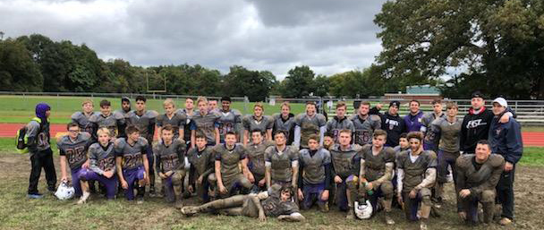 The muddy  football team poses for a team photo.