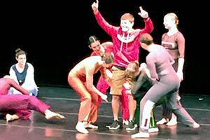 Students interact with dancers on stage.