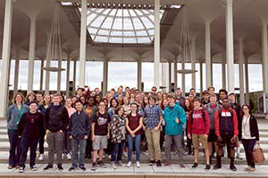 Two classes of students pose with their teachers outside the performing arts center.
