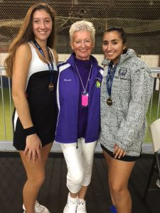 A coach and two tennis players pose for a photo