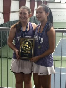 Two tennis players pose with thier award