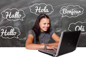 "Student at laptop. Background is a blackboard with the word ""hello"" in different languages."