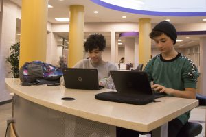 Two students work on laptops at a library table