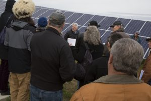 A tour group listens as Tim Holmes talks about the solar field while standing in front of a solar panel