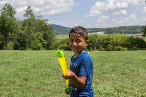 A boy fires a water gun