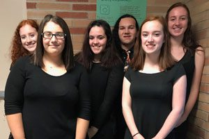 Orchestra students pose together in formal dress