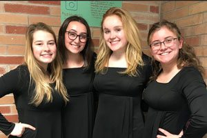 Choir members pose together in their formal dress