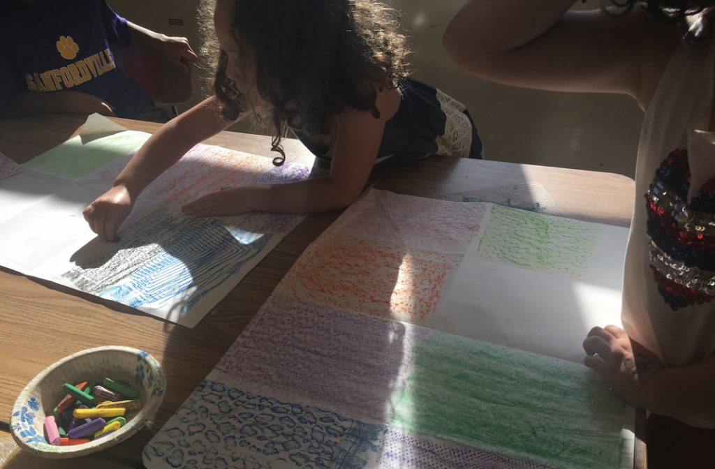 An elementary girl draws on paper with chalk