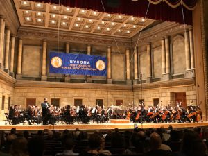 A stage view of the Eastman Theater; a strings orchestra is on stage and the NYSSMA banner hangs on the back wall.
