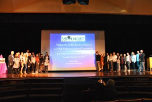 Two groups of participants in the Senior Project program pose on stage with advisors, teachers and administrators. A slide projection drop stands between two groups.