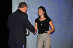 One of the advisors greets a student on stage after she announced her project.