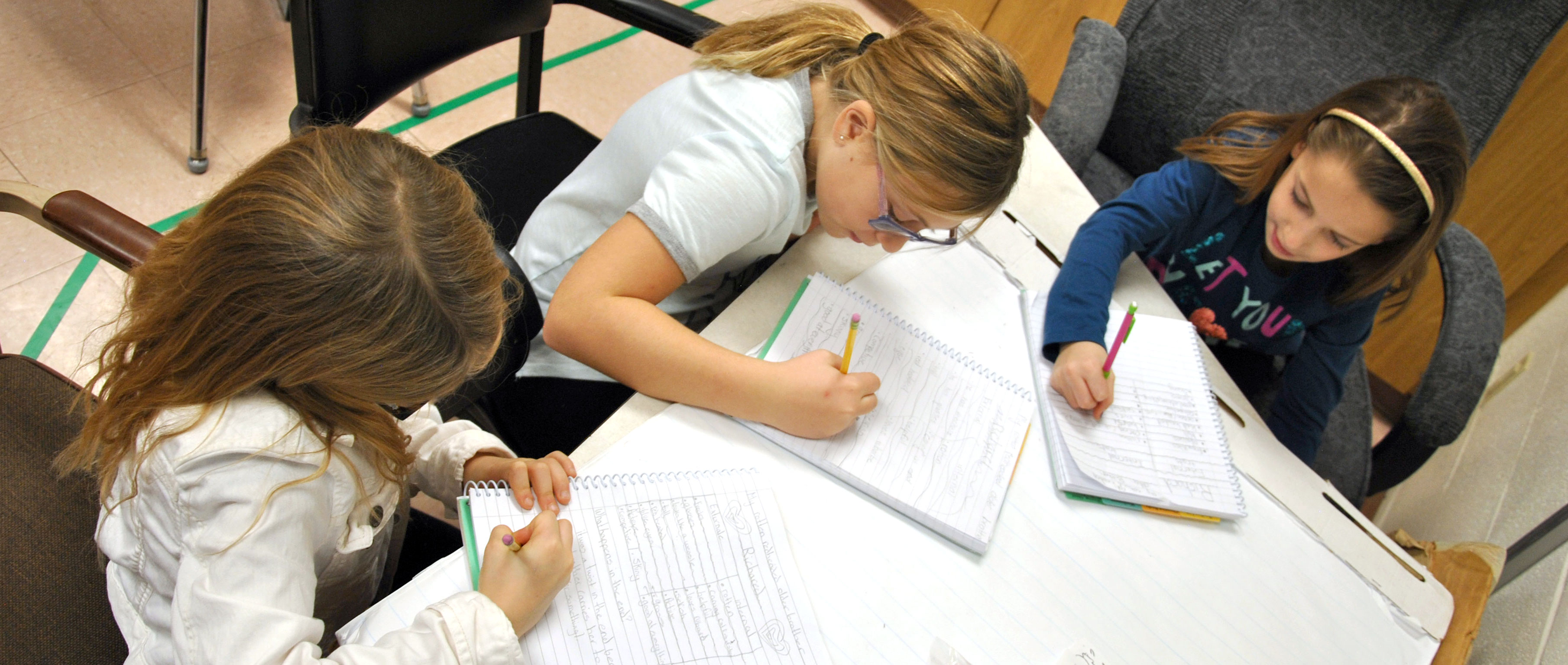 Three students write on their spiral notebooks.