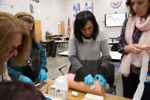A woman treats a simulated wound on a foam tube