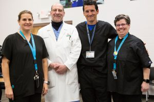 Four adults, three in black scrubs and one in a white doctor's coat, in a group portrait