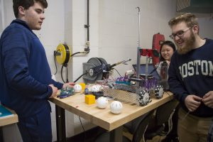 Three students work on A-B, the Robot team's creation
