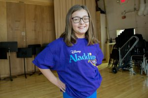 An elementary girl in an Aladdin t-shirt