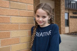 An elementary girl in a blue shirt against a brick wall