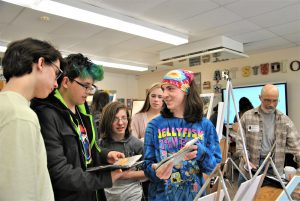 Students in a classroom look at and discuss artwork.