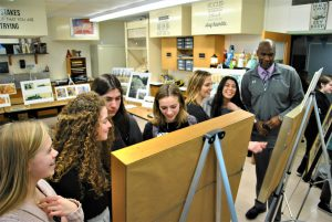 In a classroom, students and adults look at and discuss paintings propped up on easels.