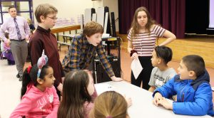 middle school students speaking to fourth-graders