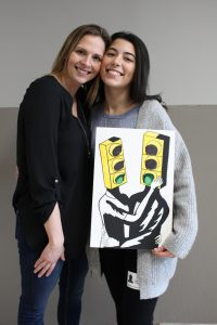 Naya and Safe Home representative with Naya's artwork