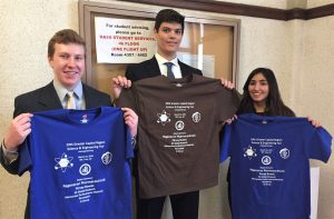 Three students holding event t-shirts.