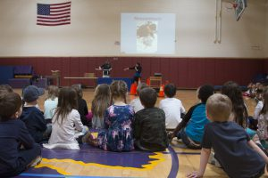 Students sit on gym floor during school assembly. Two presenters do a demonstration.