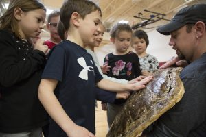 A man holds a turtle shell and students line up to touch and feel it.