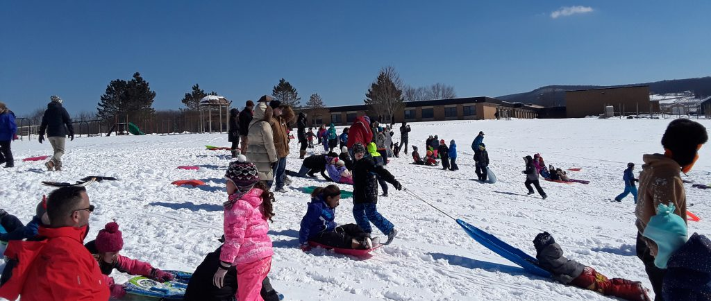 scores of students play and sled in the snow in front of the school