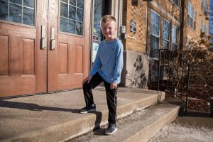 a first-grade boy standing on the school steps