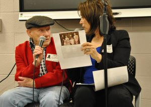 Man and woman sitting, holding microphones, seaking to each other. Woman holds a sheet of paper with an old photo of a family.