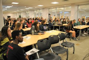 Students sitting at large tables in a conference room of the school's media center.