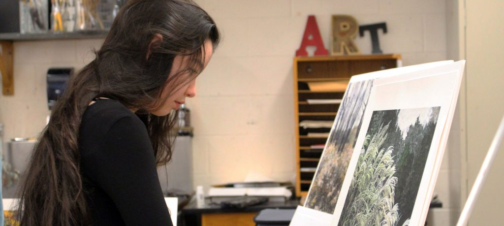 a high school girl studies a canvas