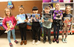 Students holding up books during the school's book fair