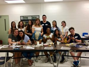 Group photo of student members of the Empty Bowls  Club. They are gathered around a table and some hold pottery bowls.